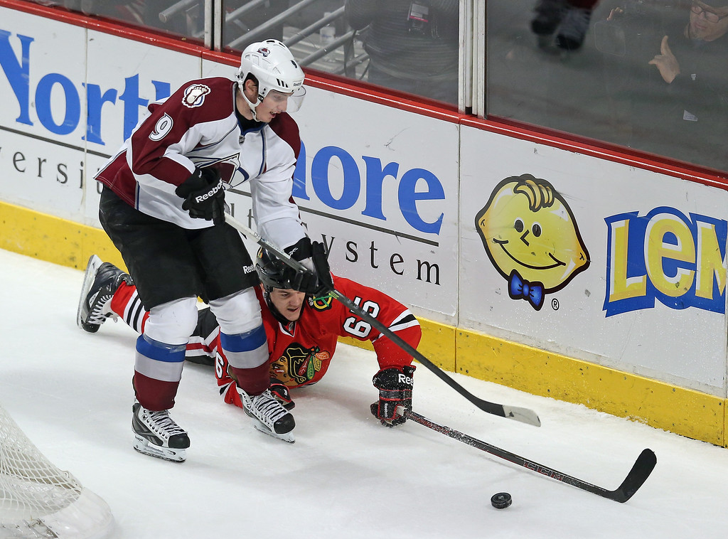. CHICAGO, IL - DECEMBER 27: Andrew Shaw #65 of the Chicago Blackhawks hits the ice battling for the puck with Matt Duchene #9 of the Colorado Avalanche at the United Center on December 27, 2013 in Chicago, Illinois. The Blackhawks defeated the Avalanche 7-2. (Photo by Jonathan Daniel/Getty Images)