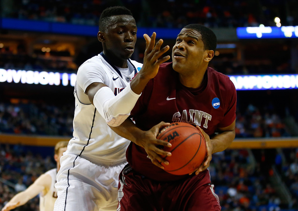 . BUFFALO, NY - MARCH 20: Ronald Roberts, Jr. #13 of the Saint Joseph\'s Hawks goes to the basket as Amida Brimah #35 of the Connecticut Huskies defends during the second round of the 2014 NCAA Men\'s Basketball Tournament at the First Niagara Center on March 20, 2014 in Buffalo, New York.  (Photo by Jared Wickerham/Getty Images)