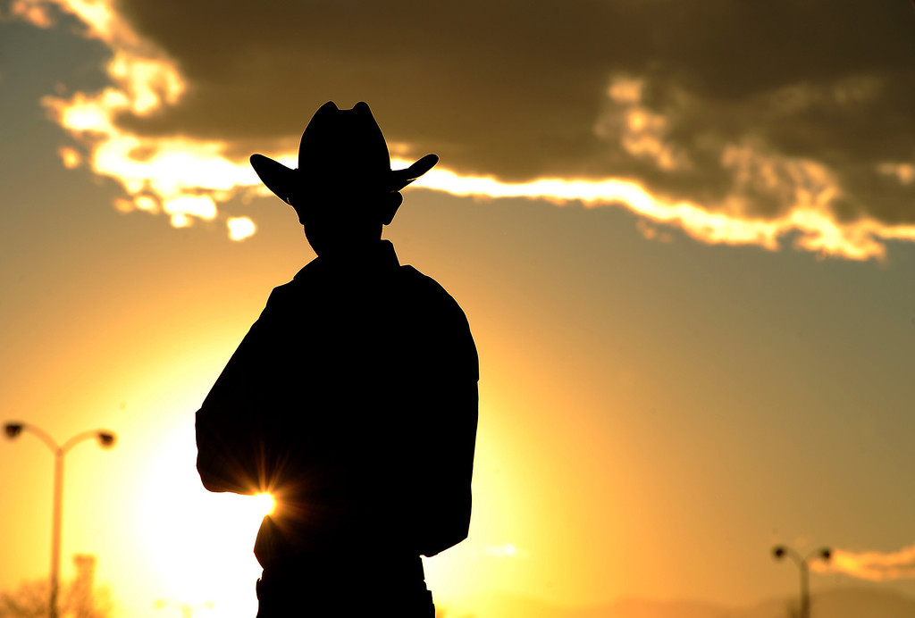 . DENVER, CO- JANUARY 27:   Logan Olson of Stephenville, Texas, watches the sunset before he packs up his trailer before heading out after the end of the stock show.  Olson participated in the team roping event of the rodeo. The final day of the 2013 National Western Stock show was Sunday, January 27th.  One of the big events for the day was the PRCA Pro Rodeo finals in the Coliseum.  The event featured bareback riding, steer wrestling, team roping, saddle bronc riding, tie down roping, barrel racing and bull riding.  (Photo By Helen H. Richardson/ The Denver Post)