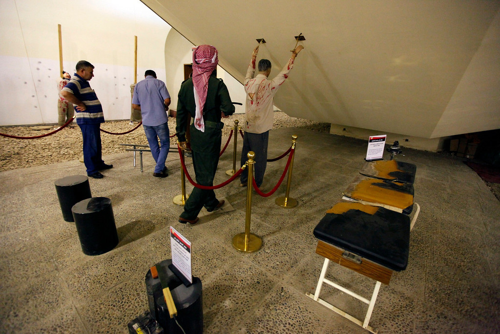 . Visitors look at torture devices, that were used by the regime of Iraq\'s ousted leader Saddam Hussein, near models re-enacting a torture scene at an exhibition gallery at the Martyrs Monument in Baghdad May 24, 2013.  REUTERS/Thaier al-Sudani