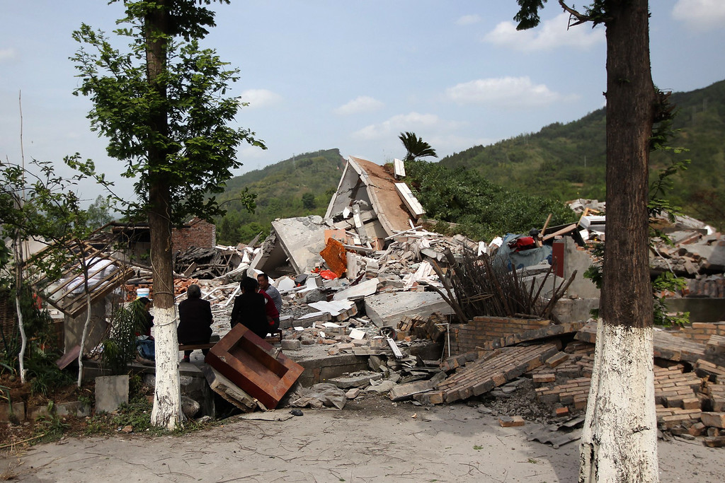 . Residents sit beside collapsed houses in Longmen township, an area close to the epicenter of a shallow 7.0 magnitude earthquake that hit the city of Ya\'an, southwest China\'s Sichuan province on April 20, 2013. More than 100 people were killed and 3,000 injured when a strong earthquake shook southwest China on April 20, wrecking homes and triggering landslides in an area devastated by a major tremor in 2008. AFP PHOTOSTR/AFP/Getty Images