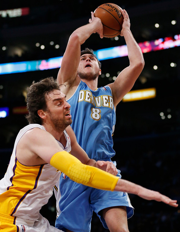 . Denver Nuggets\' Danilo Gallinari of Italy goes to the basket above Los Angeles Lakers\' Pau Gasol (L) of Spain during the first half of their NBA basketball game in Los Angeles January 6, 2013. REUTERS/Danny Moloshok