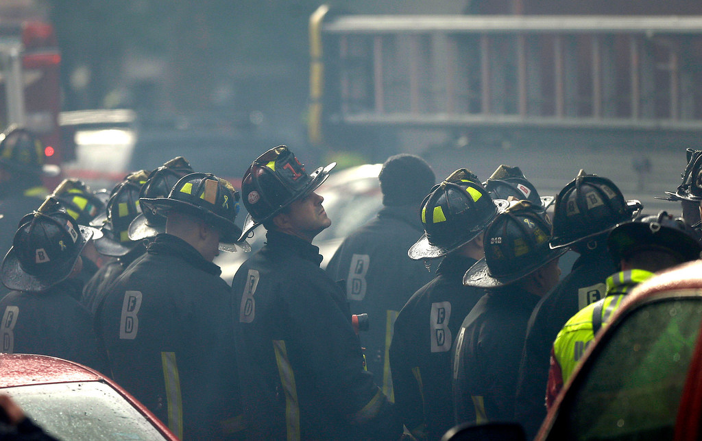 . Firefighters look on at the scene of a multi-alarm fire at a four-story brownstone in the Back Bay neighborhood near the Charles River, Wednesday, March 26, 2014, in Boston.  (AP Photo/Steven Senne)