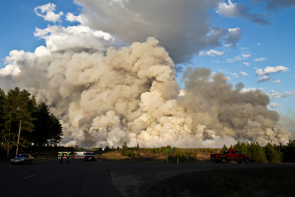 . A smoke plume rises high above a road block at the intersection of County A and Ross Road east of Solon Springs, Wis., Tuesday, May 14, 2013.  (AP Photo/The Duluth News-Tribune, Clint Austin)