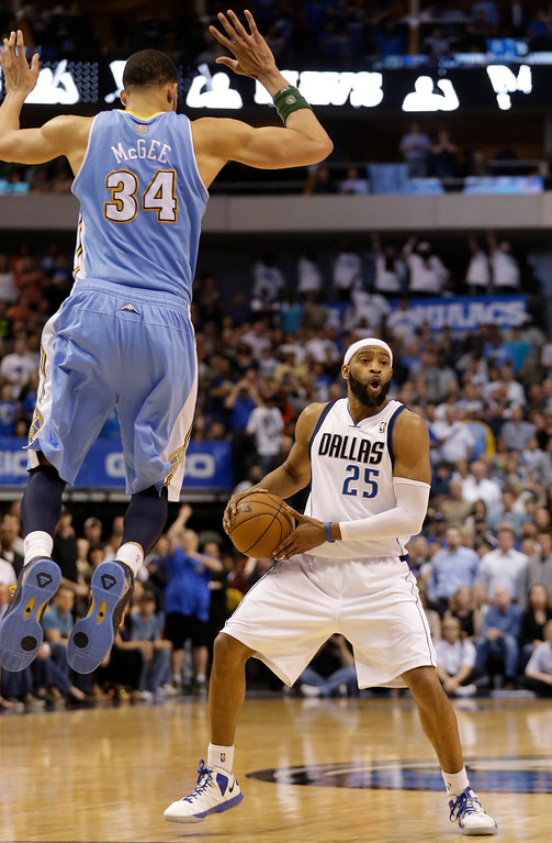. Dallas Mavericks shooting guard Vince Carter (25) looks to pass the ball against Denver Nuggets center JaVale McGee (34) during overtime play of an NBA basketball game Friday, April 12, 2013, in Dallas. The Mavericks won 108-105.  (AP Photo/LM Otero)