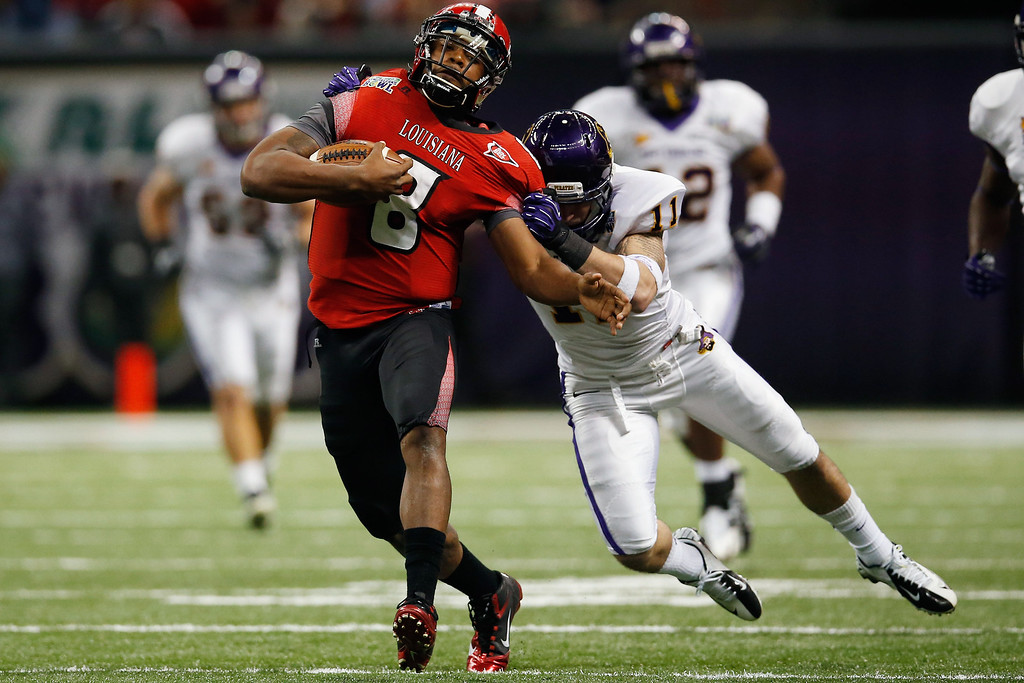 . Terrance Broadway #8 of the Louisiana-Lafayette Ragin Cajuns is tackled by Damon Magazu #11 of the East Carolina Pirates during the R+L Carriers New Orleans Bow at the Mercedes-Benz Superdome on December 22, 2012 in New Orleans, Louisiana.  (Photo by Chris Graythen/Getty Images)