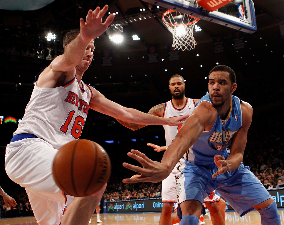 . Denver Nuggets center JaVale McGee passes around New York Knicks forward Steve Novak in the first quarter of their NBA basketball game at Madison Square Garden in New York, December 9, 2012. REUTERS/Adam Hunger