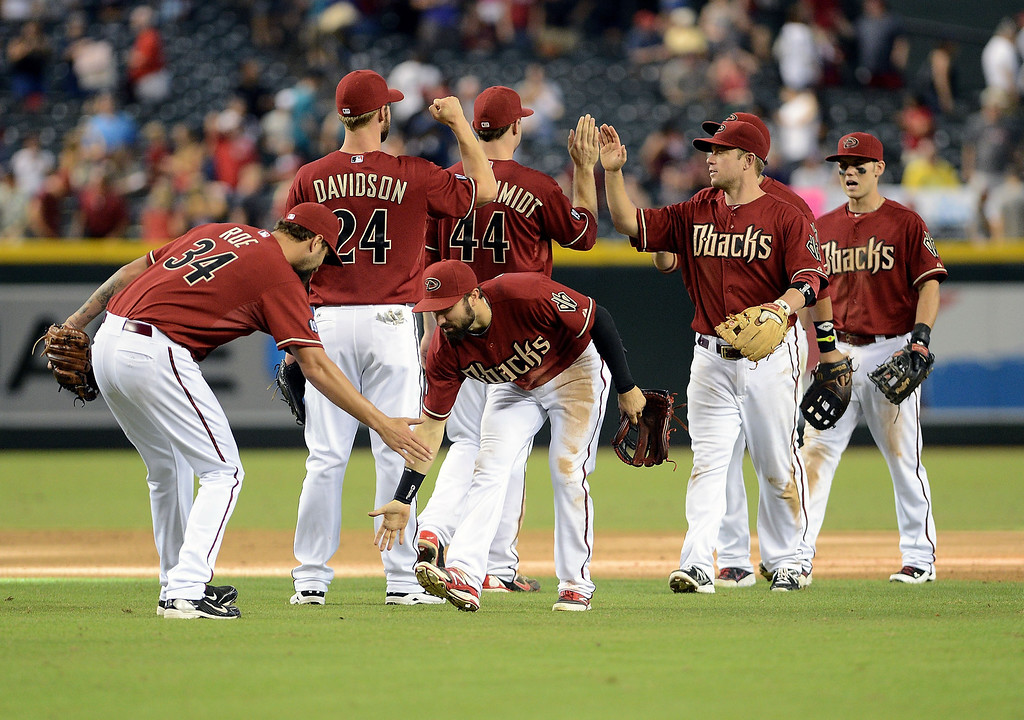 . Pitcher Chaz Roe #34 of the Arizona Diamondbacks is congratuled by outfielder Adam Eaton #6 after defeating the Colorado Rockies in the ninth inning at Chase Field on September 15, 2013 in Phoenix, Arizona. The Diamondbacks defeated the Rockies 8-2. (Photo by Jennifer Stewart/Getty Images)