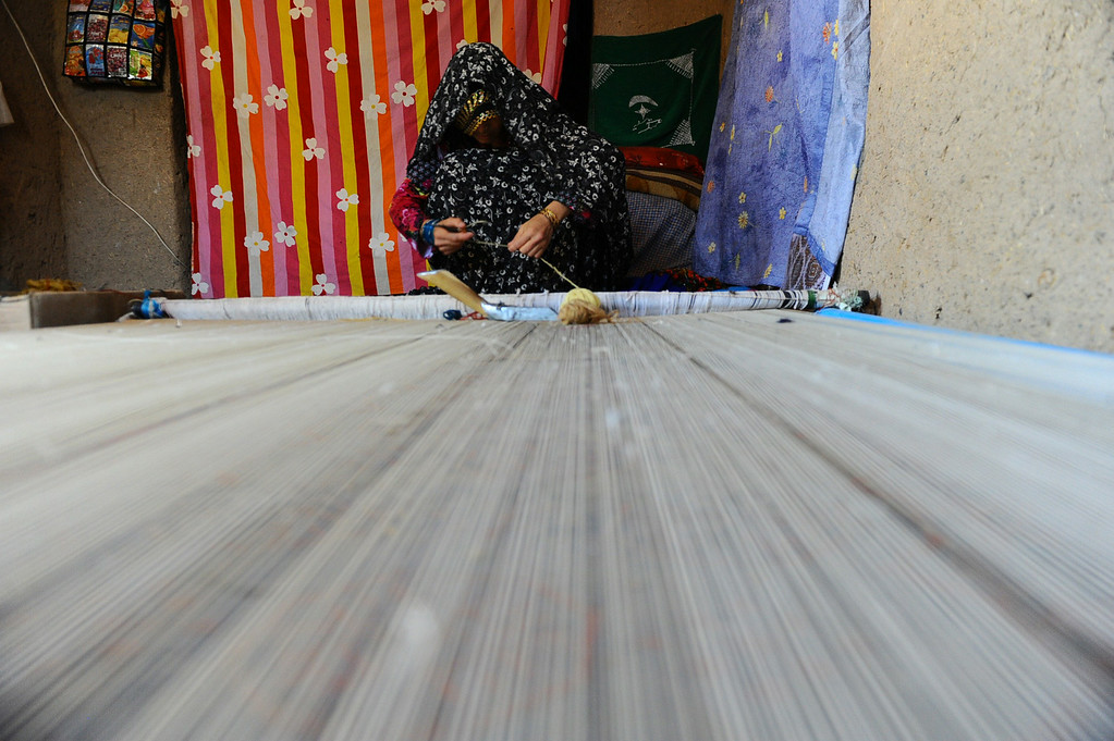 . In this picture taken on June 1, 2014, an Afghan worker weaves a carpet in a traditional factory in Zandajan district of Herat province. AFP PHOTO/Aref  Karimi/AFP/Getty Images