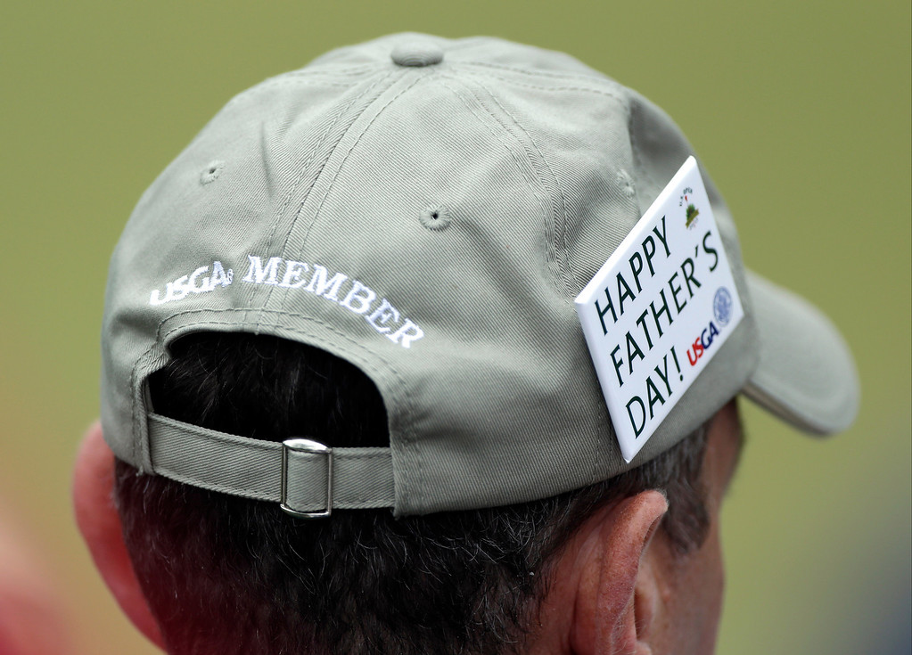 . A spectator watches play from the 17th grandstand during the fourth round of the U.S. Open golf tournament at Merion Golf Club, Sunday, June 16, 2013, in Ardmore, Pa. (AP Photo/Julio Cortez)