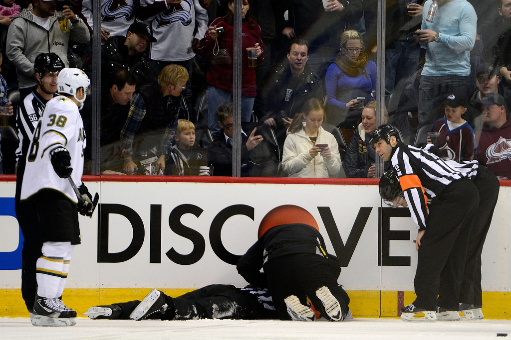 . DENVER, CO. - FEBRUARY 4: Referee Chris Rooney lies on the ice after being struck by a puck during the first period of action. Colorado Avalanche versus the Dallas Stars at the Pepsi Center on February 4, 2012. (Photo By AAron Ontiveroz/The Denver Post)