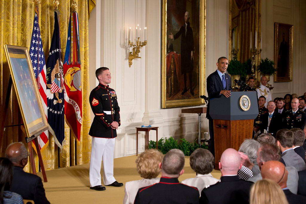 """. President Barack Obama speaks in the East Room of the White House in Washington,  Thursday, June 19, 2014, during a ceremony where he awarding retired Marine Cpl. William \""""Kyle\"""" Carpenter, 24, left, the Medal of Honor for conspicuous gallantry.  (AP Photo/Jacquelyn Martin)"""