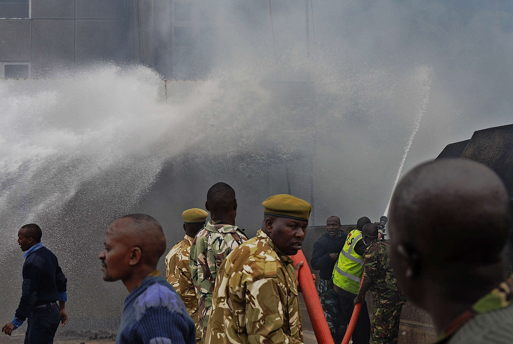 . A combined force of fire fighters, military and police spray water canon at the still smouldering terminal at the Jomo Kenyatta International airport in Nairobi on August 7, 2013.   AFP PHOTO / Tony  KARUMBA/AFP/Getty Images