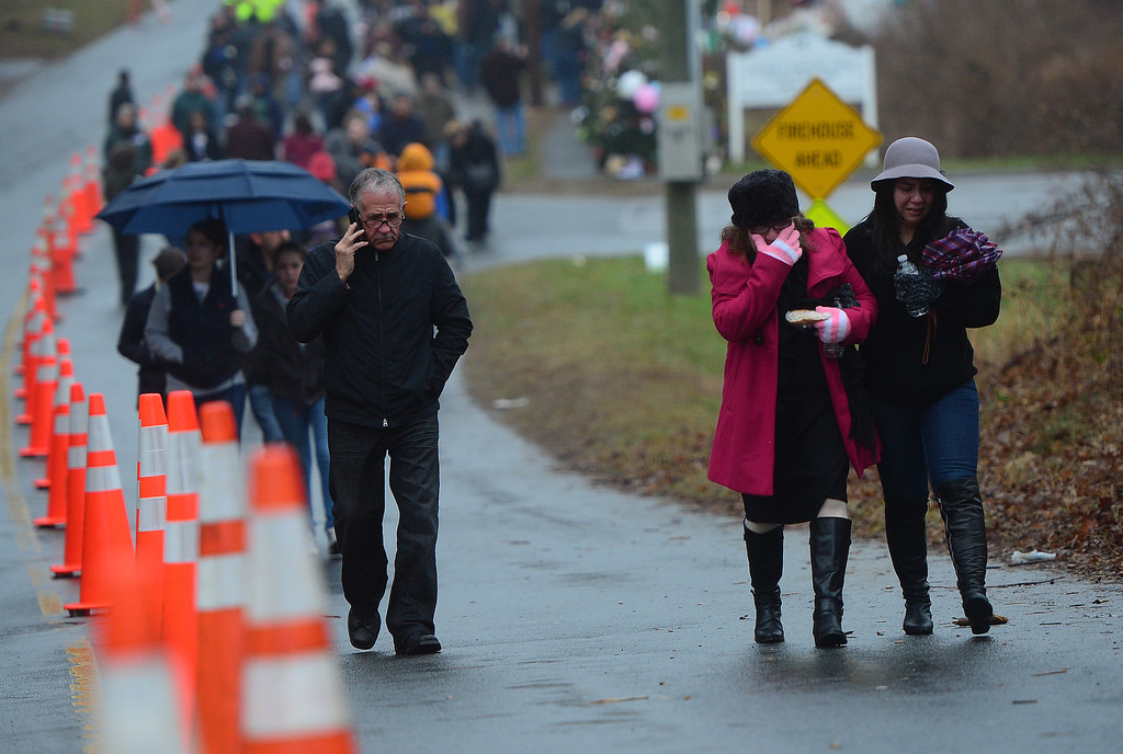 . People leave after paying their repsects at makeshift shrine to the victims of a elementary school shooting in Newtown, Connecticut, December 16, 2012.  A young gunman slaughtered 20 small children and six teachers on December 14,2012 after walking into a school in an idyllic Connecticut town wielding at least two sophisticated firearms. EMMANUEL DUNAND/AFP/Getty Images