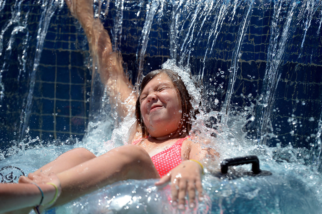 . Kate Raeder 11, rides on the lazy river and cools off under a water fall during a day at Pirates Cove July 16, 2013.  (Photo By John Leyba/The Denver Post)