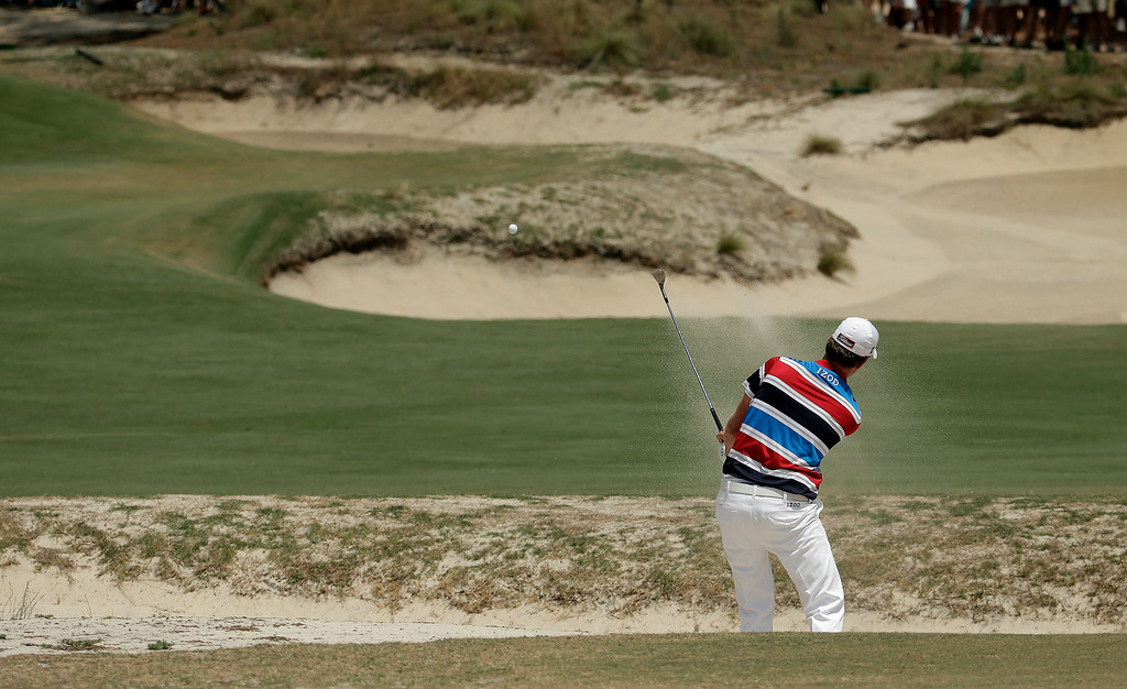 . Webb Simpson hits from the bunker on the 16th hole during the first round of the U.S. Open golf tournament in Pinehurst, N.C., Thursday, June 12, 2014. (AP Photo/Charlie Riedel)