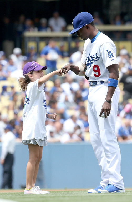 . Second baseman Dee Gordon #9 of the Los Angeles Dodgers bumps fists with a young fan before the game with the Colorado Rockies at Dodger Stadium on April 27, 2014 in Los Angeles, California. The Rockies won 6-1.   (Photo by Stephen Dunn/Getty Images)