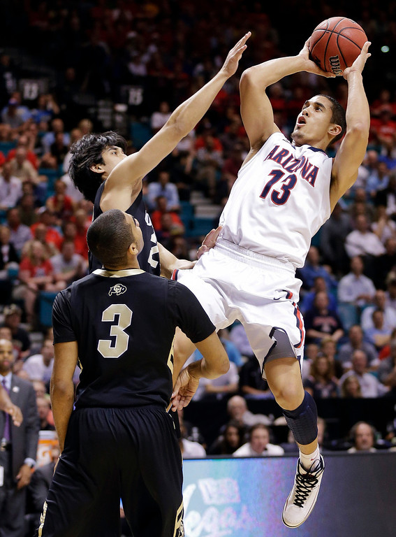 . Arizona\'s Nick Johnson (13) shoots against Colorado\'s Sabatino Chen (23) and Xavier Talton in the first half during a Pac-12 tournament NCAA college basketball game, Thursday, March 14, 2013, in Las Vegas. (AP Photo/Julie Jacobson)