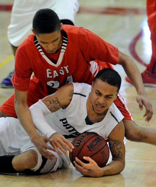 . DENVER, CO. - FEBRUARY 16: Angels guard Dominique Collier (24) wrapped up GW guard Michael Hudgens (1) as he fell to the court in the first quarter. The Denver East High School boy\'s basketball team defeated George Washington 82-20 Saturday afternoon, February 16, 2013.  (Photo By Karl Gehring/The Denver Post)