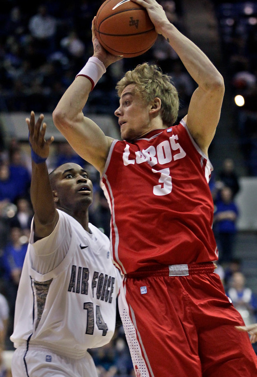 . New Mexico\'s Hugh Greenwood, right, looks to pass while covered by Air Force\'s Michael Lyons during the second half of an NCAA college basketball game in  Air Force Academy, Colo., Saturday, March 9, 2013. (AP Photo/Brennan Linsley)