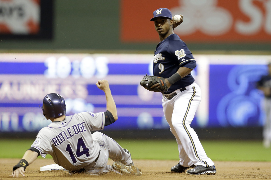 . MILWAUKEE, WI - APRIL 3:  Jean Segura #9 of the Milwaukee Brewers turns the double play as Josh Rutledge #14 slides late into second base in the top of the second inning against the Colorado Rockies at Miller Park on April 3, 2013 in Milwaukee, Wisconsin. (Photo by Mike McGinnis/Getty Images)