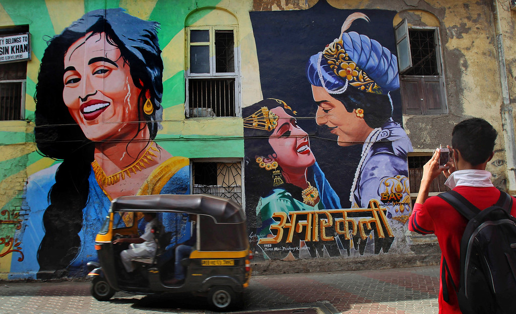 . In this April 21, 2013 photo, an  Indian youth takes a picture of a mural of indian classical moive Anarkali  in Mumbai, India. Friday, May 3 marks a hundred years after India\'s first feature film \'Raja Harischandra\', a silent movie, was screened in 1913. India produced almost 1,500 movies last year and the industry is expected to grow from $ 2 billion to $ 3.6 billion in the next five years, according to consultancy KPMG. (AP Photo/Rafiq Maqbool)