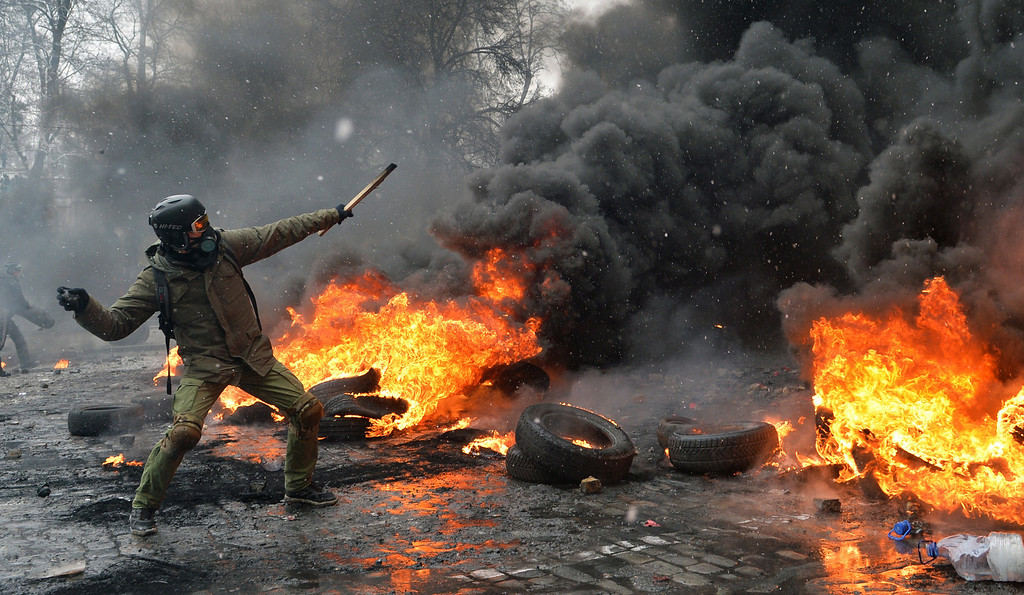 . A demonstrator throws a stone as protestors clash with police in the center of Kiev on January 22, 2014. At least two activists were shot dead today as Ukrainian police stormed protesters\' barricades in Kiev, the first fatalities in two months of anti-government protests. Pitched battles raged in the centre of the Ukrainian capital as protesters hurled stones at police and the security forces responded with tear gas and rubber bullets. AFP PHOTO / SERGEI  SUPINSKY/AFP/Getty Images