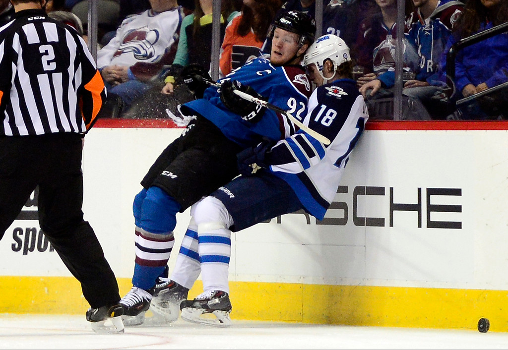 . Gabriel Landeskog (92) of the Colorado Avalanche, leans back on Bryan Little (18) of the Winnipeg Jets after checking him during the first period of action.  (Photo by AAron Ontiveroz/The Denver Post)