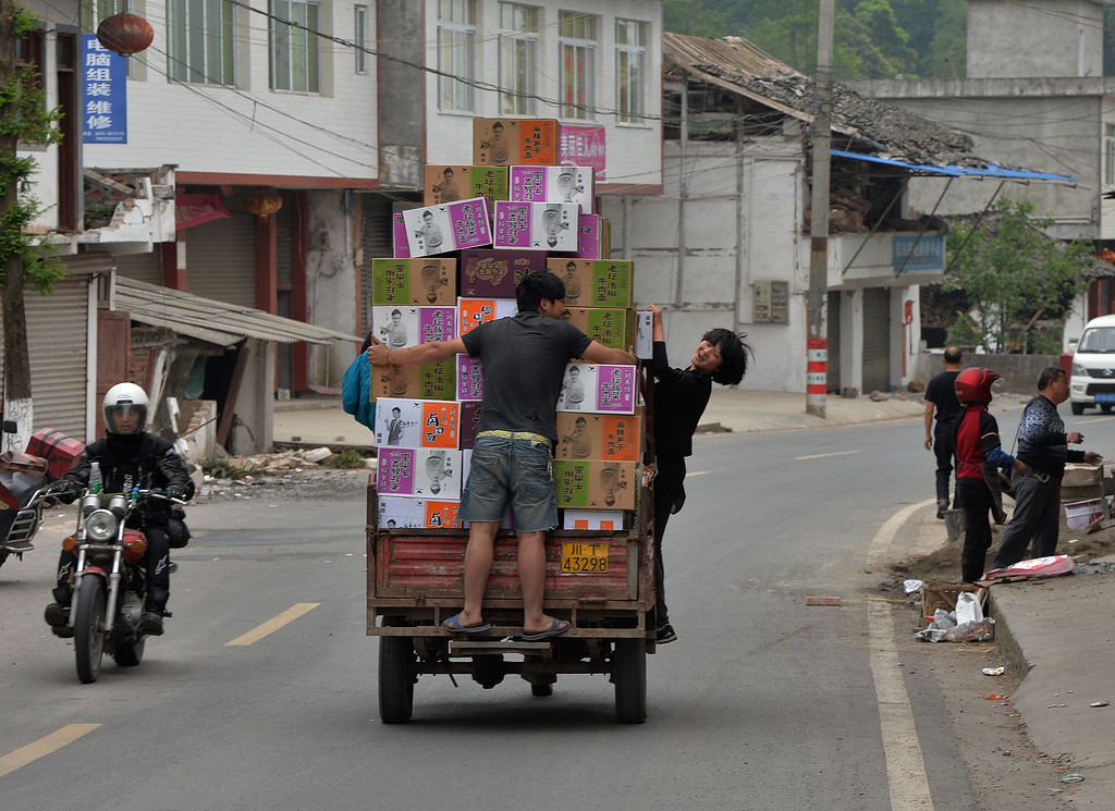 . Local residents leave a food distribution center near Longmen village after a magnitude 7.0 earthquake hit Lushan, Sichuan Province on April 22, 2013.               AFP PHOTO/Mark  RALSTON/AFP/Getty Images