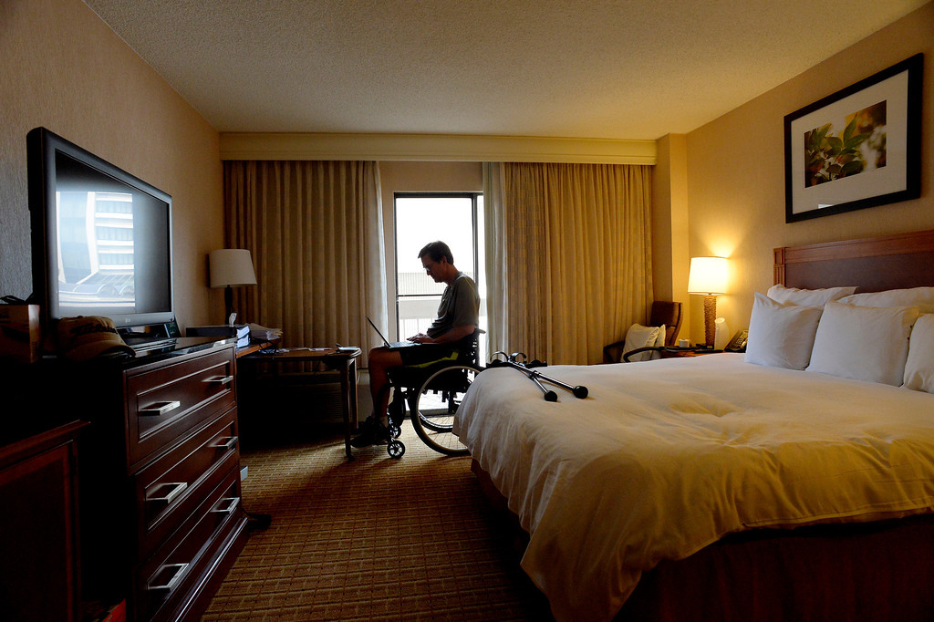 . After a morning workout at Craig Hospital Kyle checks his email in his room at the Marriott in the Denver Tech Center where he lived for 3 months. Complicating, but also probably accelerating, Pearson\'s progress was his desire to resume as much work as possible in his engineering consultancy. (Photo By Craig F. Walker / The Denver Post)