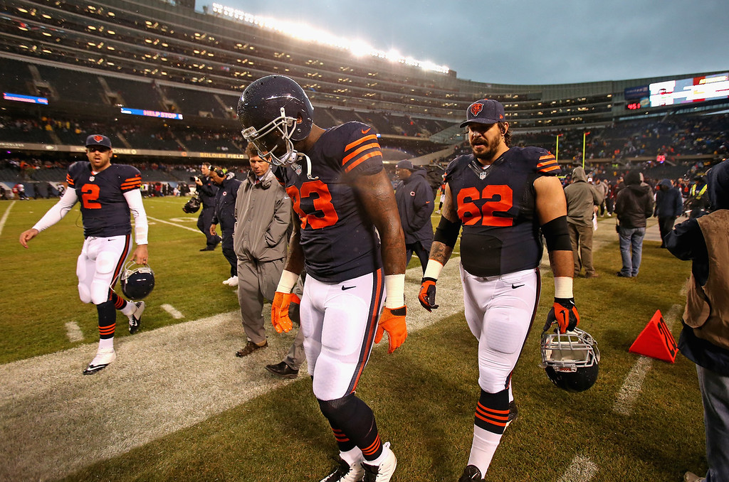 . (L-R) Jordan Palmer #2, Martellus Bennett #83 and Eben Britton #62 of the Chicago Bears leave the field as the stadium is evacuated due to weather during a game between the Bears and the Baltimore Ravens at Soldier Field on November 17, 2013 in Chicago, Illinois. A fast-moving storm system that produced at least one tornado in Illinois has produced high winds and possible flash flooding. (Photo by Jonathan Daniel/Getty Images)