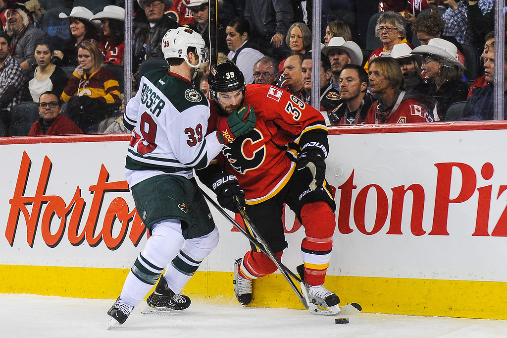 . T.J. Galiardi #39 of the Calgary Flames gets checked by Nate Prosser #39 of the Minnesota Wild during an NHL game at Scotiabank Saddledome on February 1, 2014 in Calgary, Alberta, Canada. (Photo by Derek Leung/Getty Images)