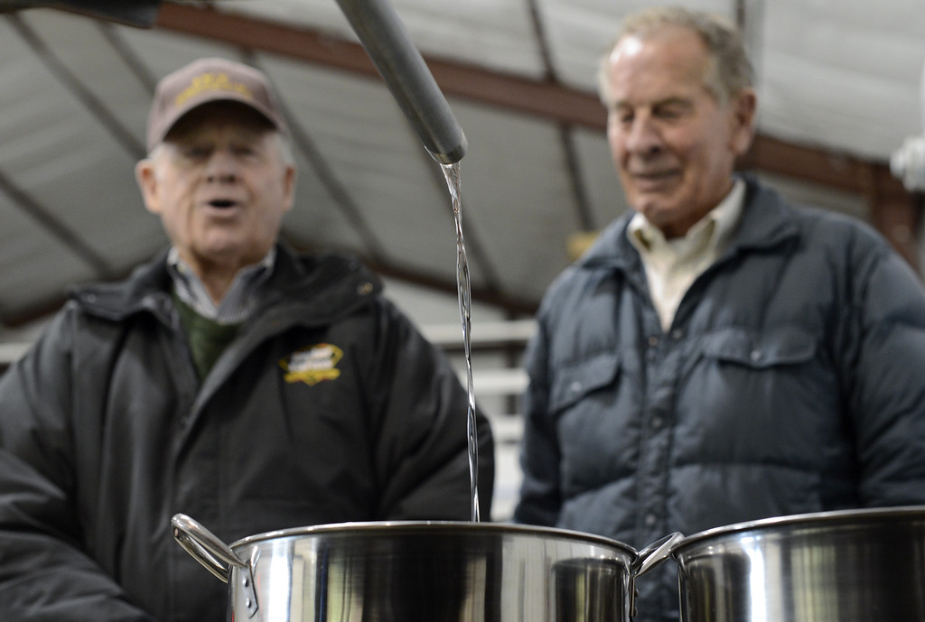 . Carlos Lovell (L), 85, and his brother Fred, 83, patiently watch their corn sour mash whiskey pour from the still at the Ivy Mountain Distillery in Mt. Airy, Georgia, USA, 26 February 2013. The Lovell family began distilling the once illegal moonshine 150 years ago in the north Georgia mountains. Carlos and Fred learned how to make moonshine when they were teenagers, and continued making the 95 proof spirits until the early 1960s, but now have resumed their craft legally.  EPA/ERIK S. LESSER