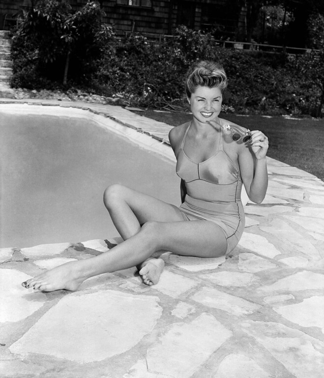 . Actress and former national swimming champion Esther Williams is shown poolside at her home in Hollywood, June 10, 1948.  Big, elaborate pools just aren\'t necessary for home use, she maintains. Her miniature measures about 20 by 30 feet. (AP Photo)
