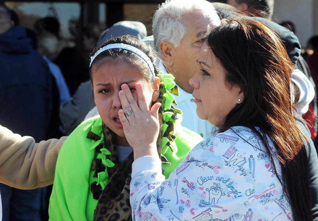 . A woman wipes a girl\'s eyes at a staging ground area set up at the Roswell Mall, where families were united after a shooting at Berrendo Middle School, Tuesday, Jan. 14, 2014, in Roswell, N.M. A shooter opened fire at the middle school, injuring at least two students before being taken into custody. (AP Photo/Roswell Daily Record, Mark Wilson)