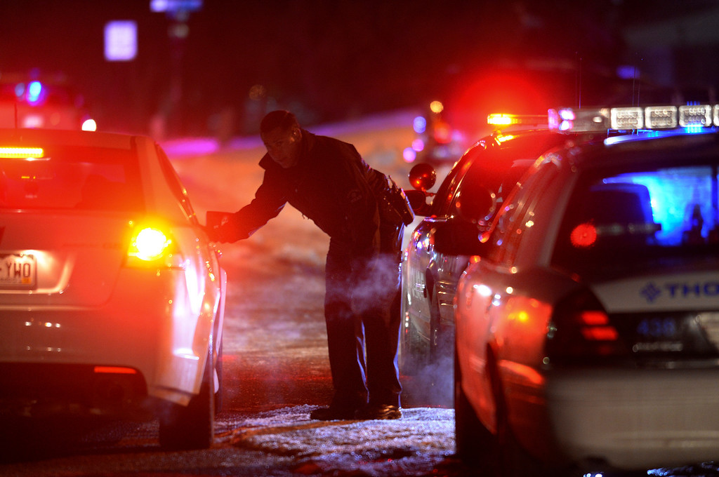 . THORNTON, CO. - FEBRUARY 7, 2014: A police officer maintained a perimeter around an apartment complex in Thornton where a murder suspect was thought to be hiding late Friday night, February 7, 2014. Authorities believe that the suspect is related to the kidnapping and possible murders of two women in Weld County. Photo By Karl Gehring/The Denver Post