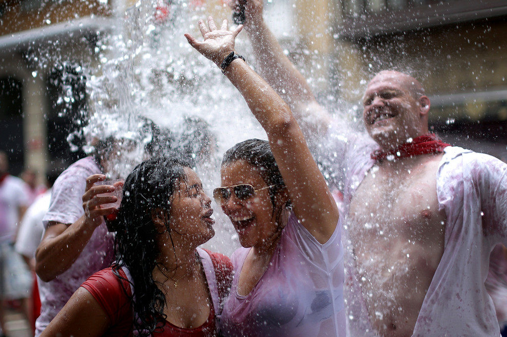 . Revellers are soaked in water and wine thrown from balconies during the opening day or \'Chupinazo\', of the San Fermin Running of the Bulls fiesta on July 6, 2014 in Pamplona, Spain. The annual Fiesta de San Fermin, made famous by the 1926 novel of US writer Ernest Hemmingway entitled \'The Sun Also Rises\', involves the daily running of the bulls through the historic heart of Pamplona to the bull ring.  (Photo by Christopher Furlong/Getty Images)