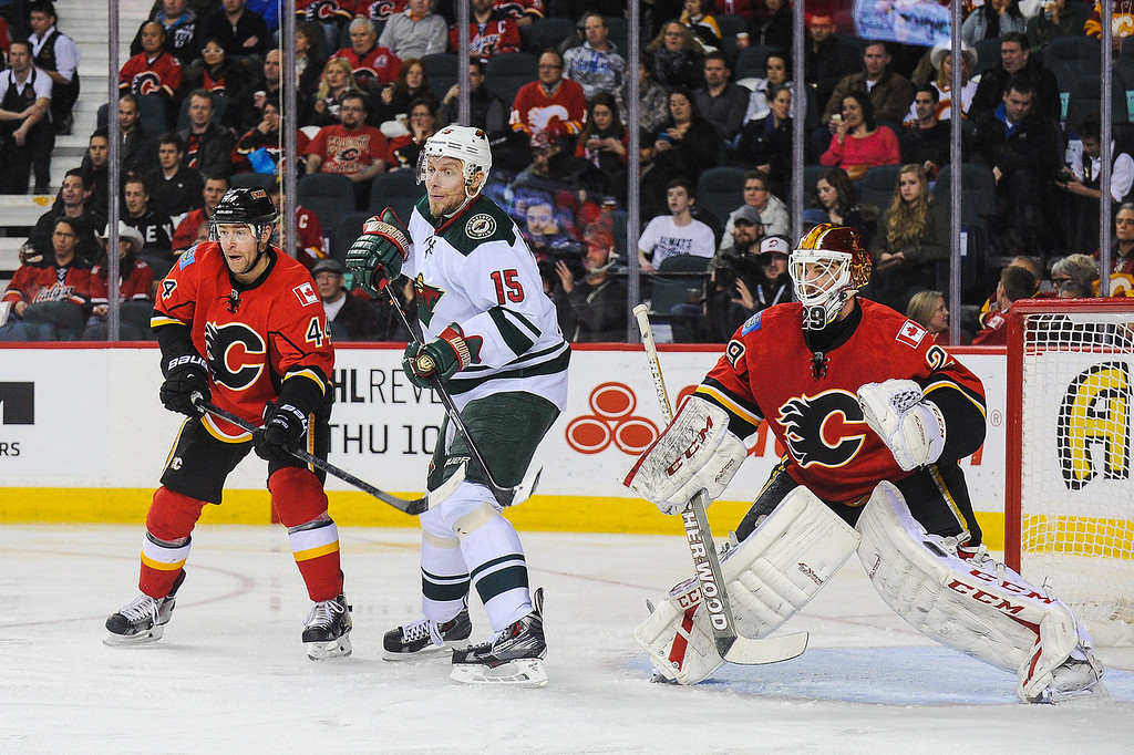 . Chris Butler #44 (L) and Reto Berra #29 (R) of the Calgary Flames defend net against Dany Heatley #15 of the Minnesota Wild during an NHL game at Scotiabank Saddledome on February 1, 2014 in Calgary, Alberta, Canada. (Photo by Derek Leung/Getty Images)