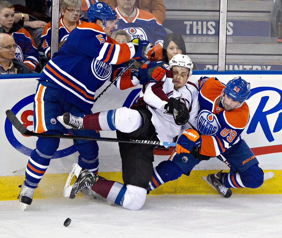 . Colorado Avalanche\'s John Mitchell, center, is checked by Edmonton Oilers\' Ladislav Smid, left, as Sam Gagner (89) looks for the puck during the second period of their NHL hockey game, Monday, Jan. 28, 2013, in Edmonton, Alberta. (AP Photo/The Canadian Press, Jason Franson)