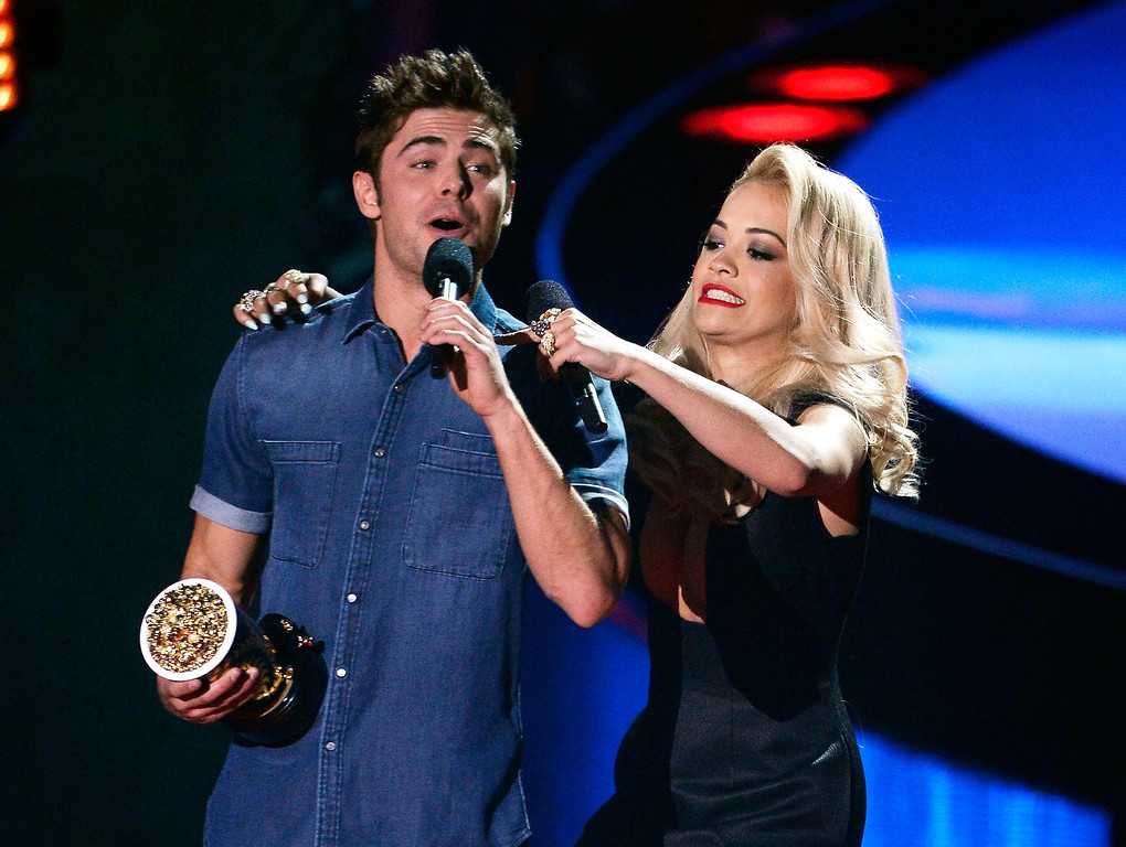. Recording artist Rita Ora (R) helps remove the shirt of actor Zac Efron, winner of the Best Shirtless Performance award for \'That Awkward Moment,\' onstage at the 2014 MTV Movie Awards at Nokia Theatre L.A. Live on April 13, 2014 in Los Angeles, California.  (Photo by Kevork Djansezian/Getty Images for MTV)