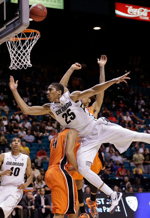 . Colorado\'s Spencer Dinwiddie (25) is fouled as he shoots against Oregon State\'s Challe Barton in the second half during a Pac-12 tournament NCAA college basketball game, Wednesday, March 13, 2013, in Las Vegas. Colorado won 74-68. (AP Photo/Julie Jacobson)