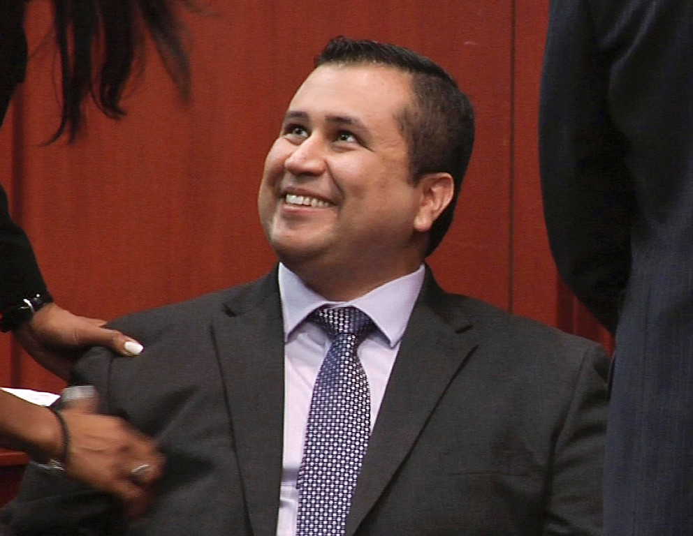. George Zimmerman smiles after a not guilty verdict was handed down in his trial at the Seminole County Courthouse, Sunday, July 14, 2013, in Sanford, Fla. Neighborhood watch captain George Zimmerman was cleared of all charges Saturday in the shooting of Trayvon Martin, the unarmed black teenager whose killing unleashed furious debate across the U.S. over racial profiling, self-defense and equal justice.  (AP Photo/TV Pool)