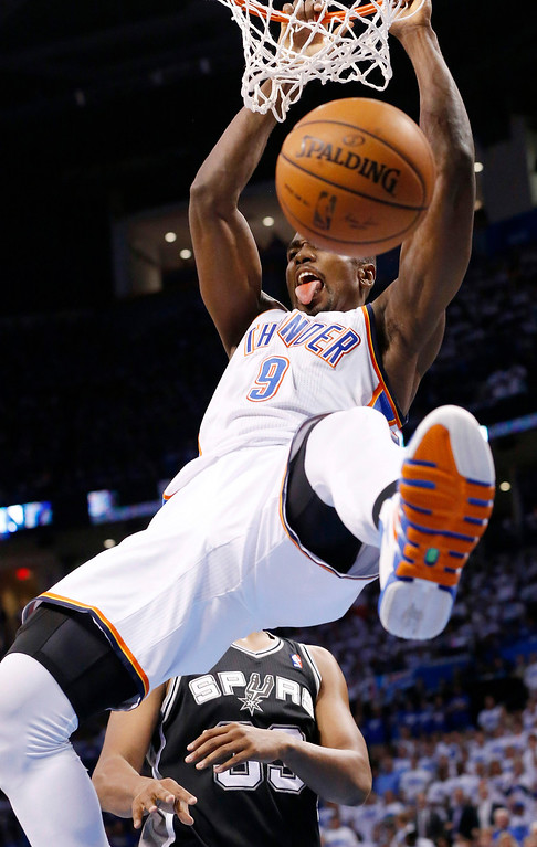 . Oklahoma City Thunder forward Serge Ibaka (9) dunks in front of San Antonio Spurs forward Boris Diaw in the second quarter of Game 4 of the Western Conference finals NBA basketball playoff series in Oklahoma City, Tuesday, May 27, 2014. (AP Photo/Sue Ogrocki)