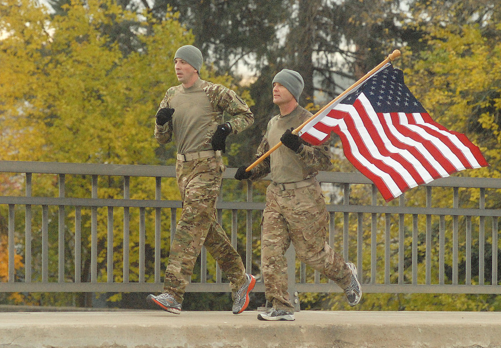 """. Les Rose, left, and Jay Via, who served in Afghanistan at different times, decided to run more than 13 miles with an American flag, Monday, Nov. 11, 2013 in Troy, Ohio. \""""We\'re doing it to honor all veterans,\"""" Rose said. (AP Photo/Anthony Weber)"""