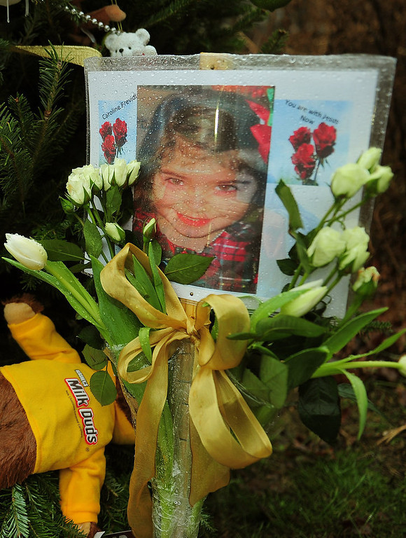 . A photo of Caroline Previdi, one of the victims of the December 14, 2012 elementary school shooting, is set up at a makeshift shrine to the victims in Newtown, Connecticut, December 17, 2012. Funerals began Monday in the little Connecticut town of Newtown after the school massacre that took the lives of 20 small children and six staff, triggering new momentum for a change to America\'s gun culture. The first burials, held under raw, wet skies, were for two six-year-old boys who were among those shot in Sandy Hook Elementary School. On Tuesday, the first of the girls, also aged six, was due to be laid to rest. There were no Monday classes at all across Newtown, and the blood-soaked elementary school was to remain a closed crime scene indefinitely, authorities said.  AFP PHOTO/Emmanuel  DUNAND/AFP/Getty Images