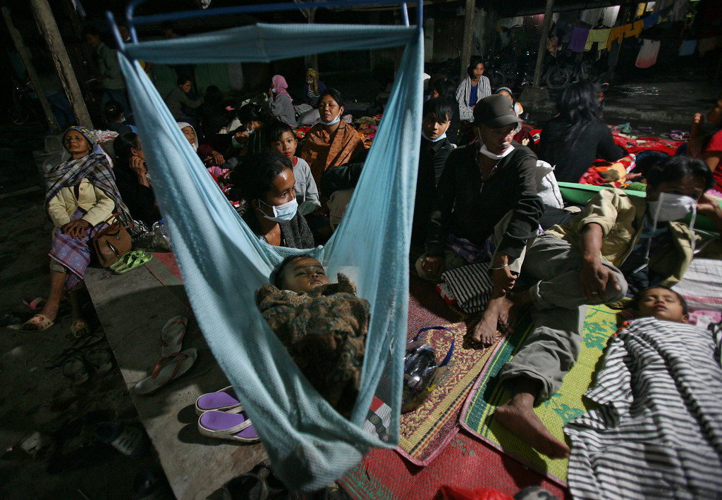 . Villagers who were evacuated from their homes following Mount Sinabung\'s eruption rest in a temporary shelter in Tiga Nderket, North Sumatra, Indonesia, Monday, Nov. 4, 2013. The 2,600-meter (8,530-foot) high volcano has been erupting since Sunday, unleashing volcanic ash high into the sky and forcing the evacuation of villagers living around its slope. (AP Photo/Binsar Bakkara)