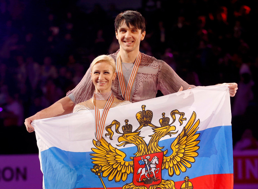 . First place finishers Tatiana Volosozhar (L) and Maxim Trankov of Russia pose with their country\'s flag during the presentation ceremony following the free skating programs at the ISU World Figure Skating Championships in London, March 15, 2013.   REUTERS/Mark Blinch