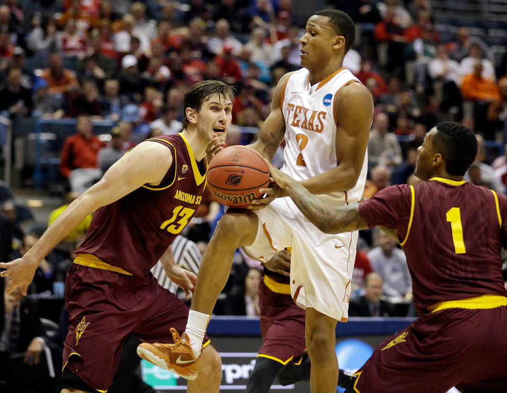 . Texas\' Demarcus Holland (2) is fouled by Arizona State\'s Jahii Carson (1) as Arizona State\'s Jordan Bachynski (13) watches during the first half of a second-round game in the NCAA college basketball tournament Thursday, March 20, 2014, in Milwaukee. (AP Photo/Jeffrey Phelps)