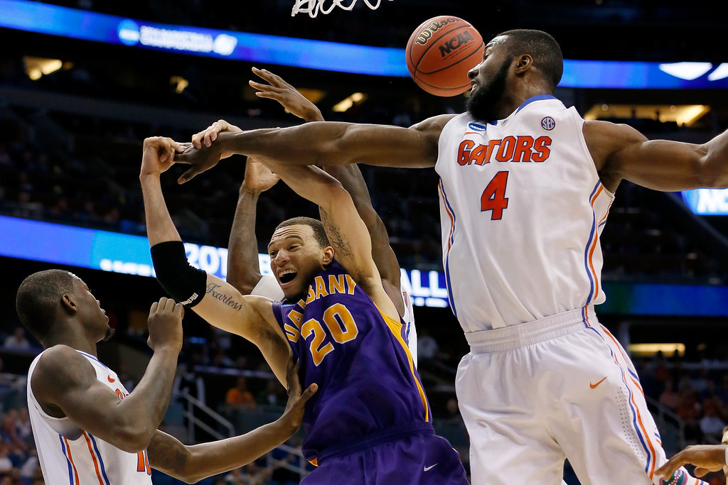 . ORLANDO, FL - MARCH 20:  Gary Johnson #20 of the Albany Great Danes goes up for a rebound against Dorian Finney-Smith #10 and Patric Young #4 of the Florida Gators in the second half during the second round of the 2014 NCAA Men\'s Basketball Tournament at Amway Center on March 20, 2014 in Orlando, Florida.  (Photo by Kevin C. Cox/Getty Images)