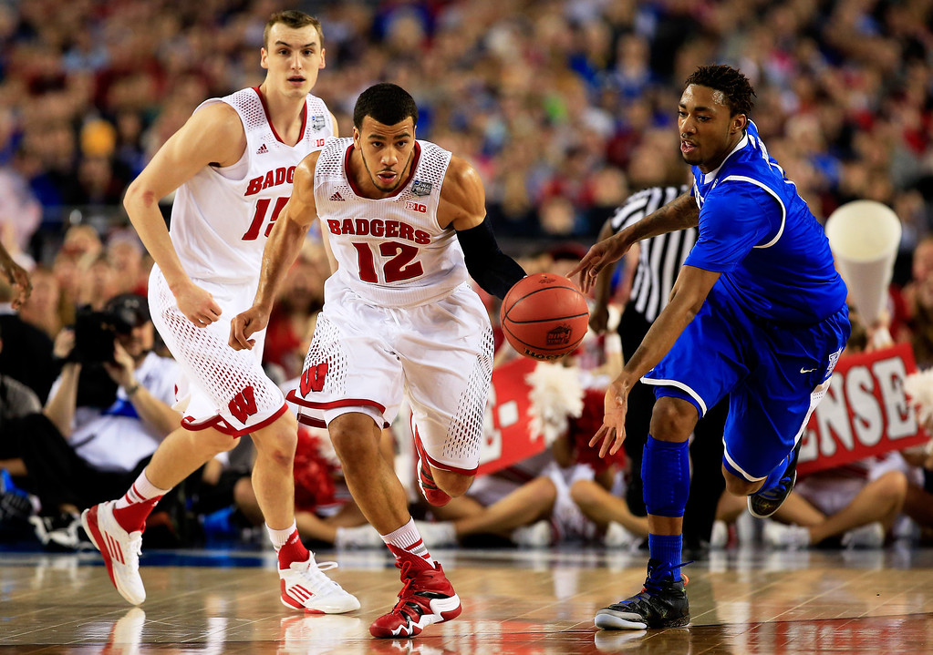 . ARLINGTON, TX - APRIL 05: Traevon Jackson #12 of the Wisconsin Badgers brings the ball up the floor as James Young #1 of the Kentucky Wildcats defends during the NCAA Men\'s Final Four Semifinal at AT&T Stadium on April 5, 2014 in Arlington, Texas.  (Photo by Jamie Squire/Getty Images)
